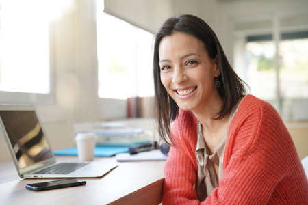 Smiling brunette woman in front of laptop