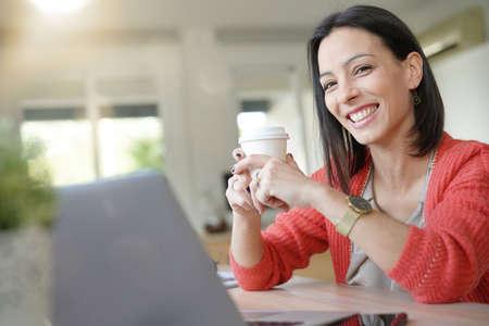 Smiling office worker drinking coffee  Standard-Bild