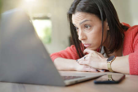 Brunette girl being tired in front of laptop computer