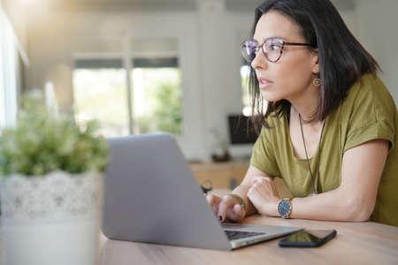 Woman in office looking by window as she is working on laptop