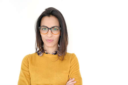 Brunette girl with eyeglasses and yellow shirt standing on white background