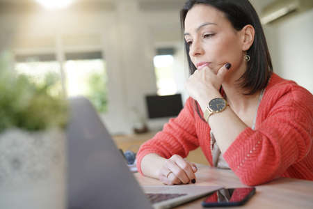 Brunette girl being thoughtful in front of laptop Standard-Bild
