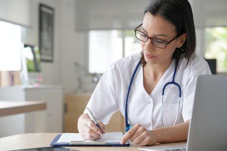 Portrait of nurse writing prescription