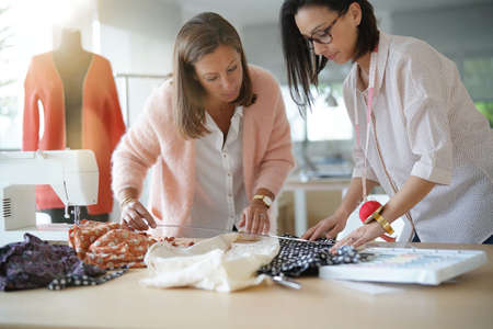 Women designers in workshop working on clothe pattern