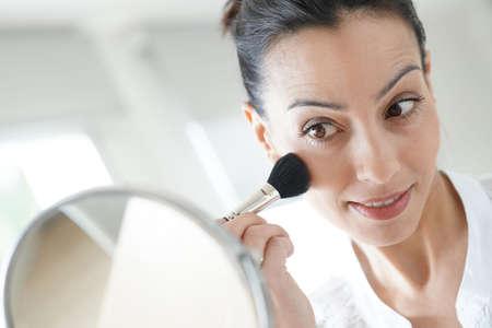 Beautiful brunette woman putting makeup on
