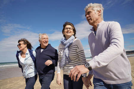 Group of senior people walking together on the beach Stock Photo
