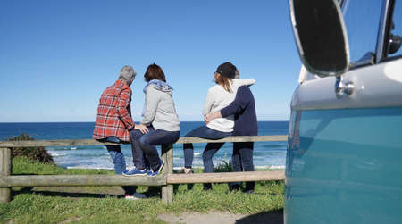 Senior friends on a road trip looking at the ocean, sit on fence