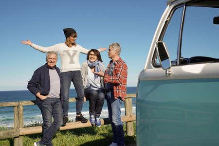 Senior people traveling with vintage camper van by the ocean