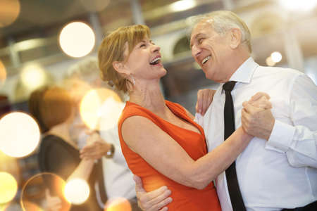 Romantic senior couple dancing together at dance hall Imagens