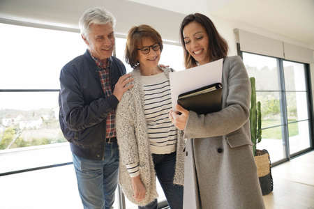 Senior couple with real estate agent visiting contemporary house