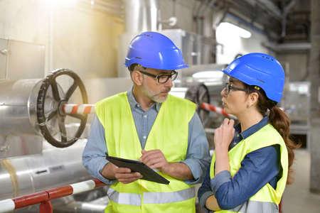 Ingénieurs industriels travaillant dans une usine de recyclage avec tablette Banque d'images - 100712682
