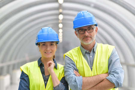 Industrial workers standing with security helmet on