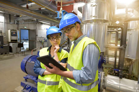 Industrial engineers working in recycling plant with tablet Reklamní fotografie - 100741071