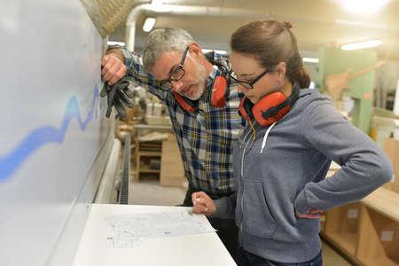 Industrial woodwork technicians programming machine Reklamní fotografie