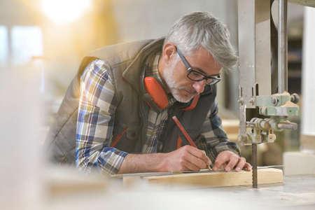 Woodworker in workshop designing piece of wood Reklamní fotografie