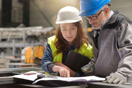Metalworker and engineer meeting in factory