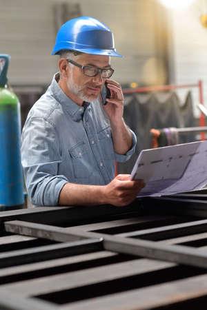 Metallurgy engineer talking on phone in factory
