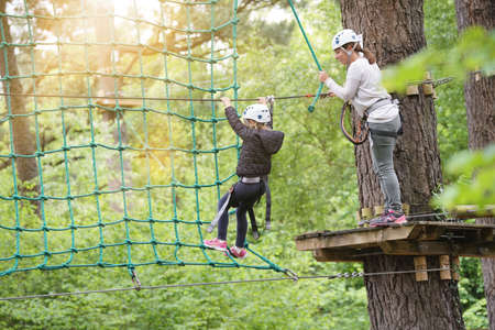 Little girl at adventure park climbing trees with secured ropes