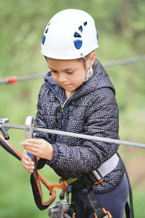 Little girl tree trekking at rope park