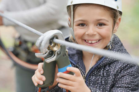 POrtrait of smilng girl testing carabiners at rope park