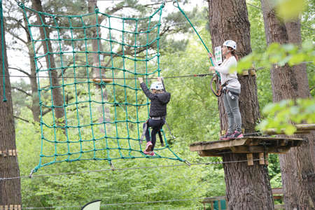 Little girl at adventure park climbing trees with secured ropes Reklamní fotografie - 101079313