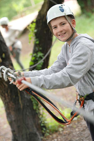 Portrait of young boy testing carabiners at rope park