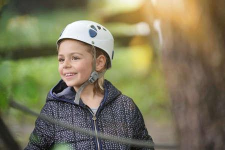 Portrait of smiling little girl wearing helmet at rope park Reklamní fotografie - 101079315