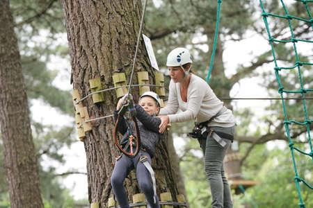 Little girl riding zip wire in trekking tree park Reklamní fotografie - 101079317