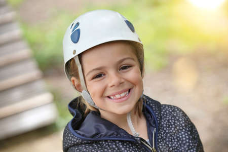 Portrait of smiling girl ready to start tree climbing course