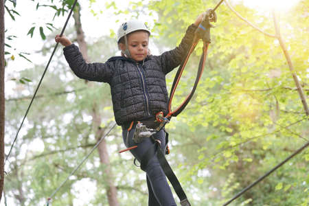 Little girl at adventure park climbing cables in trees Reklamní fotografie - 101086221