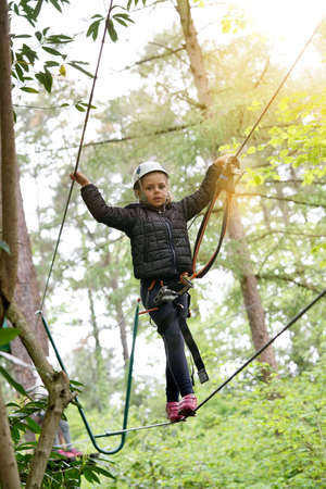 Little girl at adventure park climbing cables in trees Reklamní fotografie - 101086227