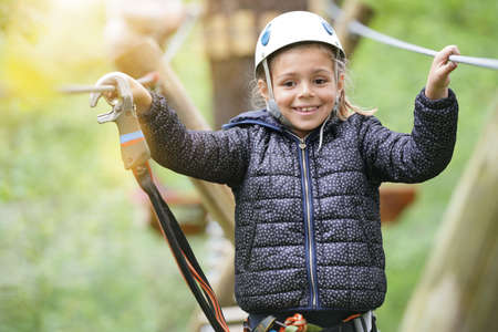 Little girl at adventure park climbing cables in trees Reklamní fotografie - 101086235