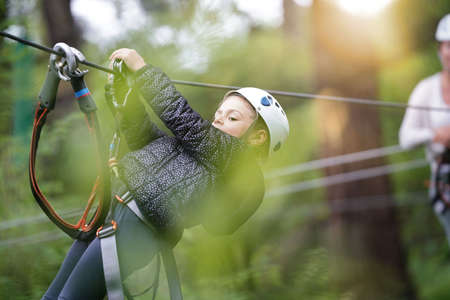 Little girl riding zip wire in trekking tree park