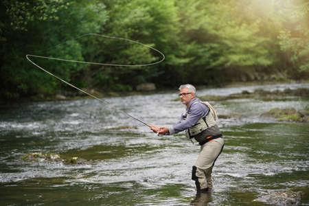 Pescador pesca con mosca en el río Foto de archivo