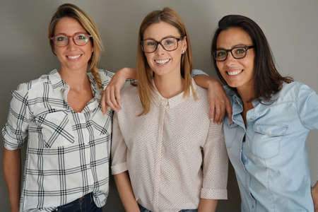 Young women with eyeglasses standing on grey background