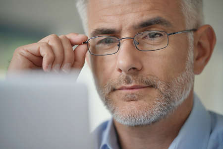 Portrait of middle-aged man with eyeglasses and grey hair