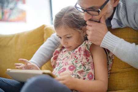 Father and daughter connected with tablet, sitting on couch Banco de Imagens