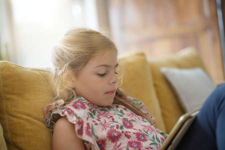 Little girl connected with tablet, sitting on couch