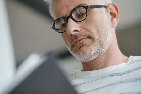 Trendy mature guy with eyeglasses reading book at home
