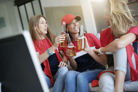 Group of friends having fun watching football game on TV