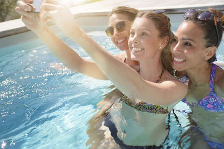 Girls in outdoor swimming-pool taking selfie pictures