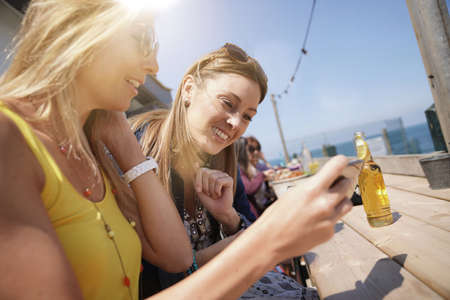 Girls sitting at beach restaurant, connected with smartphone Reklamní fotografie