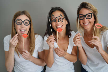 Girls having fun playing with photobooth props Foto de archivo