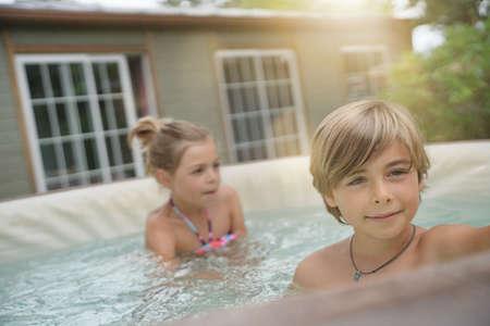 Portrait of kids enjoying hot jacuzzi water