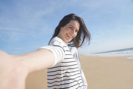 Cheerful brunette woman wallking on the beach, leading camera towards her
