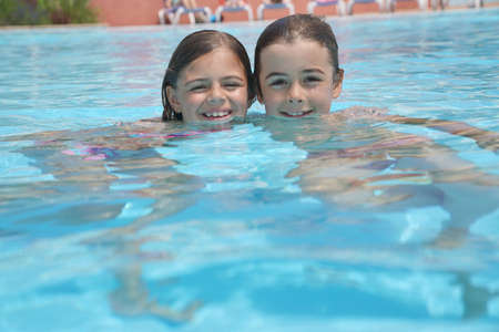 Portrait of 7-year-old kids in resort swimming-pool