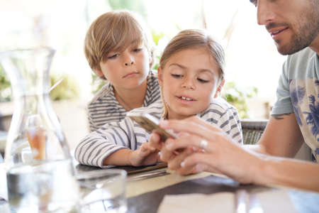 Father with kids playing with smartphone at restaurant
