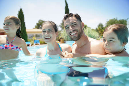 Portrait of happy family at the swimming-pool in summer