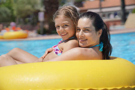 Mother and daughter riding inflatable ring at the pool Reklamní fotografie