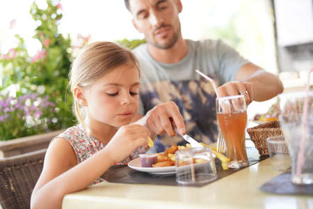 Daddy helping daughter with cutting food at restaurant Reklamní fotografie
